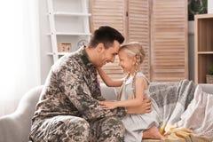 Jonge mens in militaire eenvormig met zijn kleine dochter Royalty-vrije Stock Afbeelding