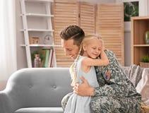Jonge mens in militaire eenvormig met zijn kleine dochter Royalty-vrije Stock Foto