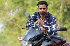 Jonge mens model status dichtbij een fiets royalty-vrije stock afbeeldingen