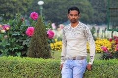 Jonge mens model status in een tuin stock fotografie