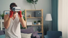 Jonge mens in moderne vergrote werkelijkheidsglazen die in flat in dozen doen die alleen opleiden stock video
