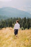 Jonge mens in modieus kostuum die zich op de zomergebied bevinden Bosheuvels bij achtergrond stock afbeelding