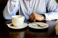 Jonge mens na een prettig theekransje die en op de telefoon in een koffie rusten spreken bedrijfslunch, commerci?le vergaderingen stock foto's
