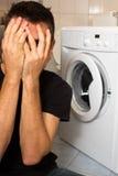Jonge mens ongelukkig met wasmashine Stock Afbeelding
