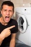 Jonge mens ongelukkig met wasmashine royalty-vrije stock afbeelding