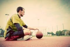 Jonge mens op basketbalhof Het zitten en het druppelen Royalty-vrije Stock Fotografie