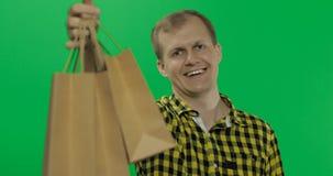 Jonge mens op de groene zeer belangrijke achtergrond van de het schermchroma met het winkelen zakken royalty-vrije stock foto