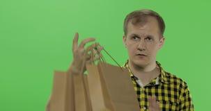 Jonge mens op de groene zeer belangrijke achtergrond van de het schermchroma met het winkelen zakken stock video