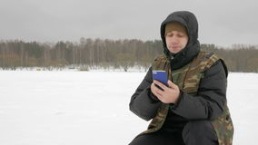 Jonge mens op een bevroren meer met een telefoon die de gewenste route zoeken Hij trekt op zijn ardingen stock videobeelden