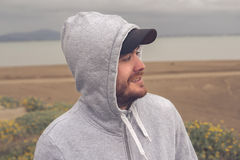 Jonge mens op het strand die een hoodie en een honkbal GLB dragen Stock Fotografie