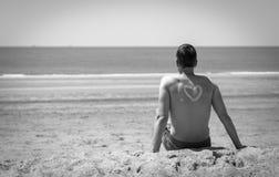 Jonge mens op het strand in zwart-wit stock fotografie