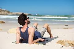 Jonge mens op vakantiezitting alleen bij een afgezonderd strand stock foto's