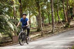 Jonge mens op zijn bergfiets bij het bos Stock Foto's