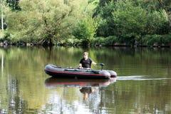 Jonge mens in opblaasbare boot met visserij bij rivier Royalty-vrije Stock Fotografie