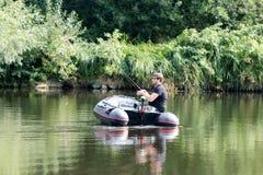 Jonge mens in opblaasbare boot met visserij bij rivier Stock Foto