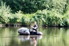 Jonge mens in opblaasbare boot met visserij bij rivier Stock Fotografie
