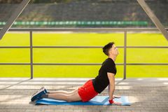 Jonge mens opleidingsyoga in openlucht De sportieve kerel maakt uitrekkende oefening op een blauwe yogamat, op de sportengrond stock foto
