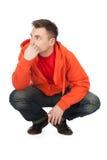 Jonge mens in oranje sweatshirt, volledige lengte Royalty-vrije Stock Afbeelding