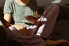 Jonge mens in pyjama's die een tabletcomputer met behulp van Royalty-vrije Stock Foto