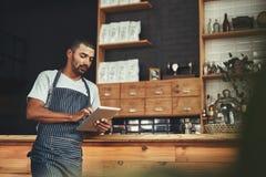 Jonge mens in schort die digitale tablet gebruiken bij zijn koffie stock afbeeldingen