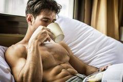 Jonge mens shirtless op zijn bed met een koffie of theekop royalty-vrije stock foto's