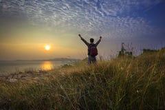 Jonge mens status en het toenemen hand als overwinning op grasheuvel die aan zon boven overzees horizontaal met dramatische kleurr Royalty-vrije Stock Afbeelding