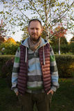 Jonge mens in sweater en jeans die dichtbij berk in het park blijven Royalty-vrije Stock Foto