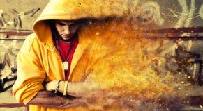 Jonge mens in sweatshirt met een kap op grungemuur Deeltjeseffect Royalty-vrije Stock Fotografie