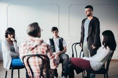 Jonge mens toegeven die dat hij alcoholisch tijdens de vergadering van de steungroep is royalty-vrije stock fotografie
