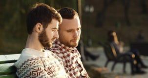 Jonge Mens twee die Laptop met behulp van terwijl het Zitten in outdor op bank 4K stock videobeelden