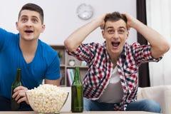 Jonge mens twee die op TV letten Royalty-vrije Stock Foto