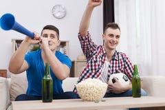 Jonge mens twee die op TV letten Royalty-vrije Stock Afbeelding