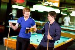 Jonge mens twee het roosteren met een bier stock fotografie
