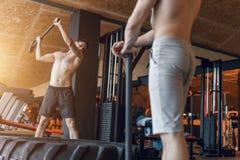 Jonge mens twee met een hamerstaking op een band in de gymnastiek workout Royalty-vrije Stock Fotografie