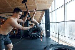 Jonge mens twee met een hamerstaking op een band in de gymnastiek workout Stock Foto's