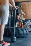 Jonge mens twee met een hamerstaking op een band in de gymnastiek workout Royalty-vrije Stock Foto