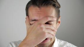 Jonge mens in wanhoop die behandelend zijn gezicht met zijn hand schreeuwen stock videobeelden