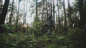 Jonge mens in zich in het bos bevinden en camouflage die rond eruit zien Jagersmannetje die het grondgebied op de aard onderzoeke stock videobeelden