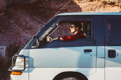 Jonge mens in zijn auto of het kamperen bestelwagen stock foto