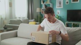 Jonge mens in zijn de doospakket van het woonkamer openingskarton stock videobeelden