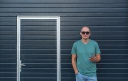 Jonge mens in zonnebril met telefoon tegen de achtergrond van een muur en de gesloten deuren Royalty-vrije Stock Afbeeldingen