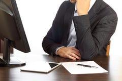 Jonge mens in zwart kostuum bij zijn die bureau op witte achtergrond wordt geïsoleerd Royalty-vrije Stock Afbeeldingen