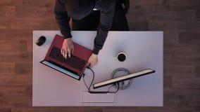 Jonge mens in zwarte hoodiezitting achter op laptop typen en dan bureau die, die weglopen wanneer de lichten tijdens nacht aanzet stock video