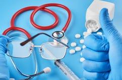 Jonge menselijke de pillentabletten van de handgreep in palm Gezondheidszorg, medische en farmaceutische concept Op blauwe achter stock afbeelding
