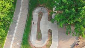 Jonge mensen die in het groene park op de weg in cirkel met een skateboard rijden stock video