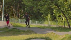 Jonge mensen die in het groene park op speciale golvende weg voor skateboarders met een skateboard rijden stock video