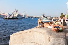 Jonge mensen die op de waterkant op de achtergrond van warshi ontspannen Royalty-vrije Stock Foto