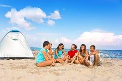 Jonge mensen die op strand kamperen royalty-vrije stock afbeelding