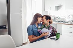 Jonge mensen gifting boeket van bloemen aan zijn meisje in keuken Het gelukkige paar koesteren Romantische Verrassing stock foto