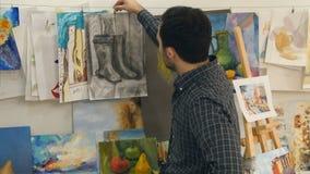 Jonge mensen hangende schilderijen op koord in kunstklasse royalty-vrije stock foto's